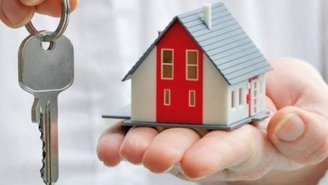 Persona mostrando una llave y una casa